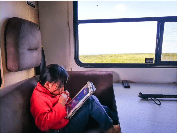 Child inside RV playing on tablet